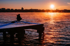 People on the pier watching the sunset .Silhouette of fishermen. Royalty Free Stock Photos