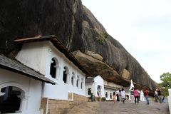 People, pilgrims, and tourists around the Dambulla Cave Temple stock photo