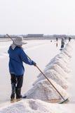 People piling up sea salt Royalty Free Stock Photo