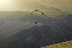 People planning on a parachute against the backdrop of beautiful mountains and sunset. People planning on a parachute in the background of beautiful mountains Stock Photography