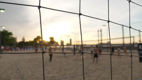 People Play Beach Volleyball on Pier 25 in Manhattan at Sunset. 10400 An extreme shallow depth of field slow motion view of people playing beach volleyball at stock video