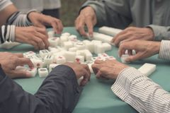 People play a board game. Mahjong board game. Playing Mahjong on table. People play a board game in the park royalty free stock photo