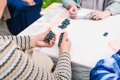 People play dominoes. Several people have fun playing dominoes on the street. Board game stock image