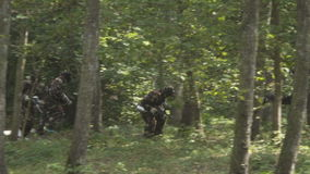 People play paintball in the woods stock video footage