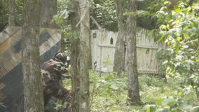 People play paintball in the woods stock footage