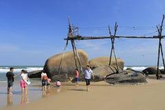 People play under wood bridge of rock beach Stock Image