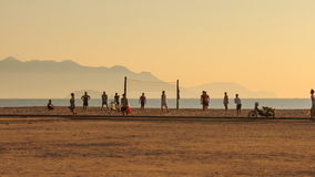 People play volleyball on beach against sea hills at sunrise. NHA TRANG, KHANH HOA/VIETNAM - AUGUST 03 2015: Vietnamese people play volleyball on sand beach near stock video footage