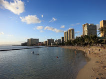 People play in water and beach in Waikiki at dusk Royalty Free Stock Images