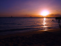 People play in water with dramatic Sunset on Kaimana Beach Royalty Free Stock Image