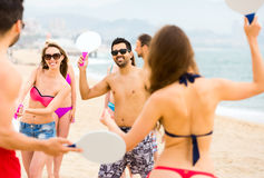 People playing active games on beach stock images