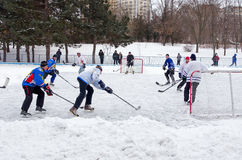 People playing amateur hockey in the city Ice skating rink. Winter playing, fun, snow Royalty Free Stock Photos