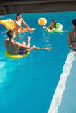 People playing with ball in swimming pool Stock Photos