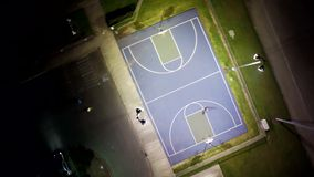 People playing basketball on a court at night stock video