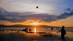 People playing on beach at sunset