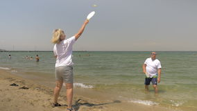 People Playing Beach Tennis by the Seaside. Slow motion shot of mature man and woman playing beach tennis, man is standing in the sea water, woman is on the sand stock footage