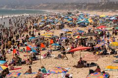 People playing at the beach under colorful umbrellas royalty free stock photo