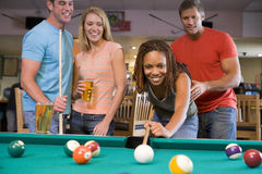 People Playing Billiards. Two smiling young couples playing billiards in a bowling alley bar. Night Out concept stock photo
