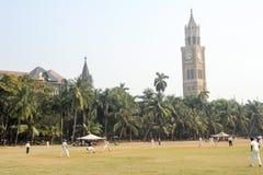 People playing cricket in front of Rajabai Tower at Mumbai Royalty Free Stock Photo