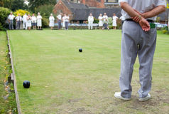 People playing Flat Lawn Bowls. Men and women playing Flat Lawn Bowls. The man in the foreground is the skip and stands at the head end where he shouts royalty free stock photos