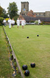 People playing Flat Lawn Bowls. Men and women playing Flat Lawn Bowls in a english village overlooked by the local church. Focus on the three bowls in the stock photos