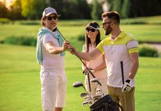 People playing golf. Two men and a women are choosing golf clubs, talking and smiling while standing on golf course Royalty Free Stock Images
