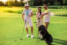 People playing golf. Two men and a women are choosing golf clubs, talking and smiling while standing on golf course Stock Image