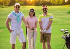 People playing golf. Two men and a women are holding golf clubs, looking at camera and smiling while standing on golf course Royalty Free Stock Photography