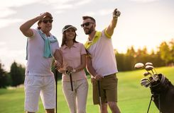 People playing golf. Two men and a women are holding golf clubs, talking and smiling while standing on golf course Royalty Free Stock Photo