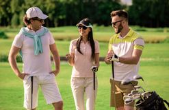 People playing golf. Two men and a women are holding golf clubs, talking and smiling while standing on golf course Stock Photos