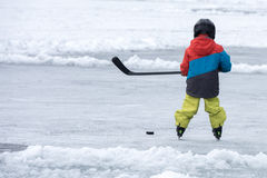 People playing hockey on frozen lake Royalty Free Stock Photo