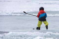 People playing hockey on frozen lake Royalty Free Stock Image