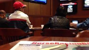 People playing horse racing gambling game. Inside Hard Rock Casino in Coquitlam BC Canada stock video