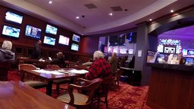 People playing horse racing gambling game. Inside Hard Rock Casino in Coquitlam BC Canada stock footage