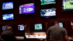 People playing horse racing gambling game inside Hard Rock Casino