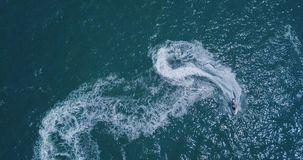 People are playing a jet ski in the sea. Aerial view stock photography