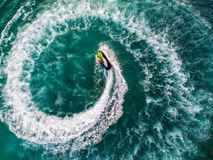People are playing a jet ski in the sea.Aerial view. Top view.am. Azing nature background.The color of the water and beautifully bright. Fresh freedom. Adventure Royalty Free Stock Photography