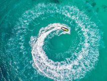 People are playing a jet ski in the sea.Aerial view. Top view.am. Azing nature background.The color of the water and beautifully bright. Fresh freedom. Adventure Royalty Free Stock Image