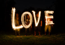 People playing lighting in the word love Stock Photo