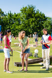 People playing miniature golf outdoors. People, men and women, playing miniature golf on a beautiful summer day Stock Photography
