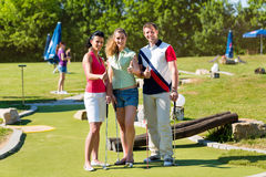People playing miniature golf outdoors. People, men and women, playing miniature golf on a beautiful summer day Royalty Free Stock Image
