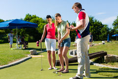 People playing miniature golf outdoors. People, men and women, playing miniature golf on a beautiful summer day Stock Images
