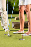 People playing miniature golf outdoors. People, man and woman, only feet, playing miniature golf on a beautiful summer day Stock Photos