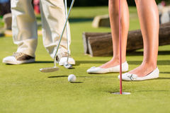 People playing miniature golf outdoors. People, man and woman, only feet, playing miniature golf on a beautiful summer day Royalty Free Stock Photography
