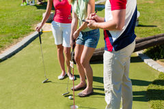 People playing miniature golf outdoors Royalty Free Stock Images