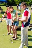 People playing miniature golf outdoors. People, man and women, playing miniature golf on a beautiful summer day Royalty Free Stock Photography