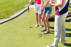 People playing miniature golf outdoors. People, man and women, playing miniature golf on a beautiful summer day Royalty Free Stock Photos