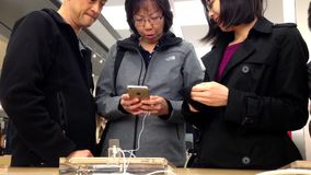 People playing new iphone inside Apple store stock footage