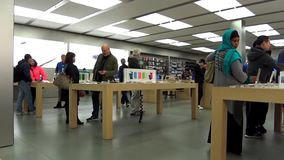People playing new iphone inside Apple store, shot with fisheye lens. Stock Photos
