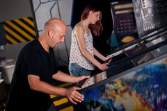 People playing pinball at arcade. In game room Stock Image