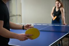 People playing ping pong tennis at gym room stock images